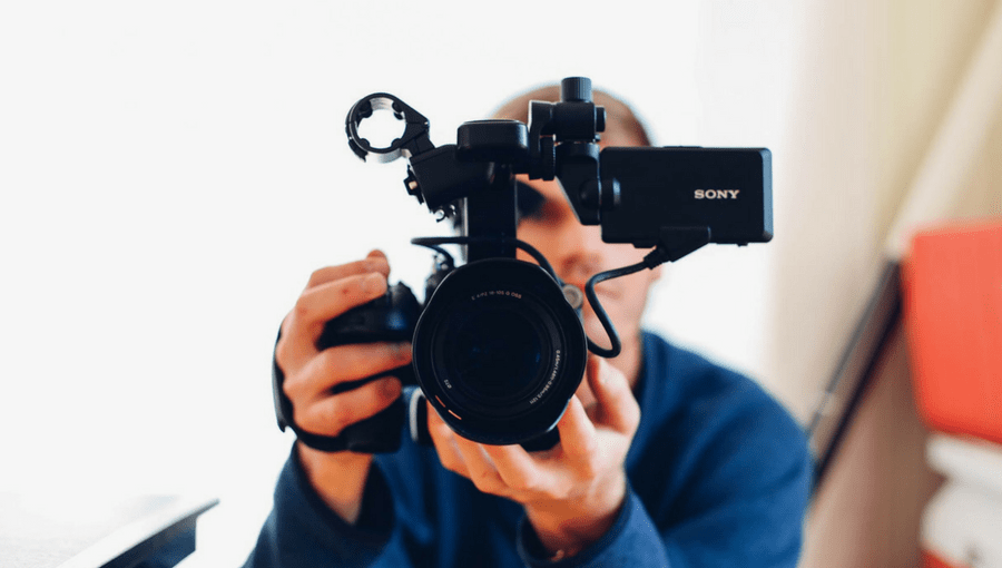 A man pointing a video camera at you