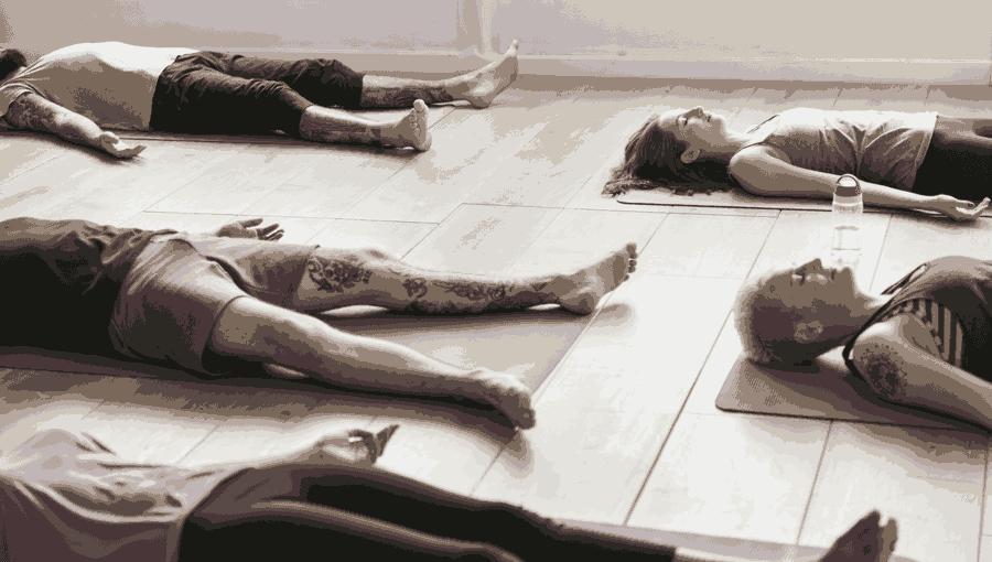 A yoga class engaged in Savasana