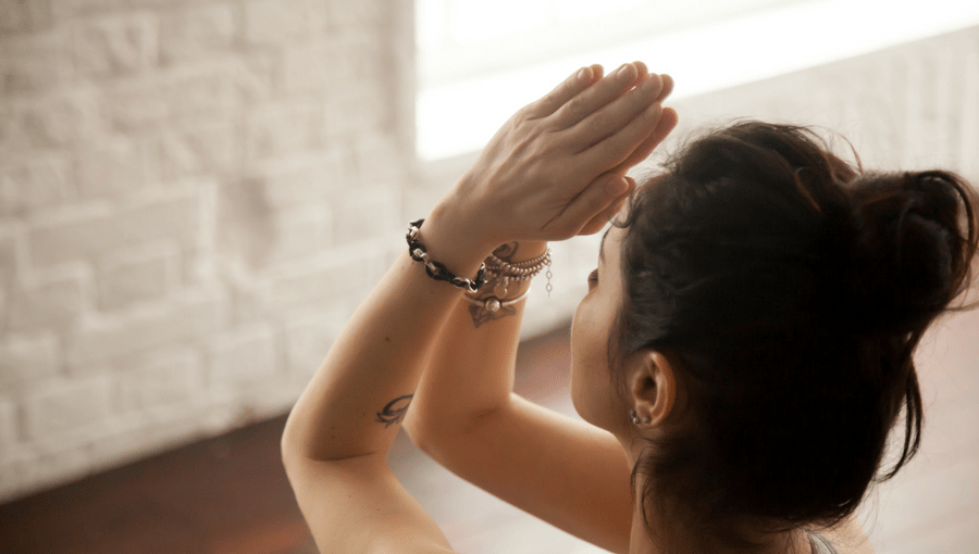 A girl in yoga class doing Namaste