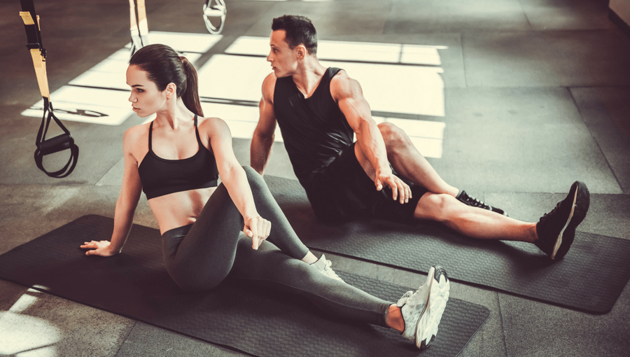 A fit couple practising yoga in a gym