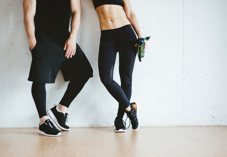 A couple standing in workout clothes
